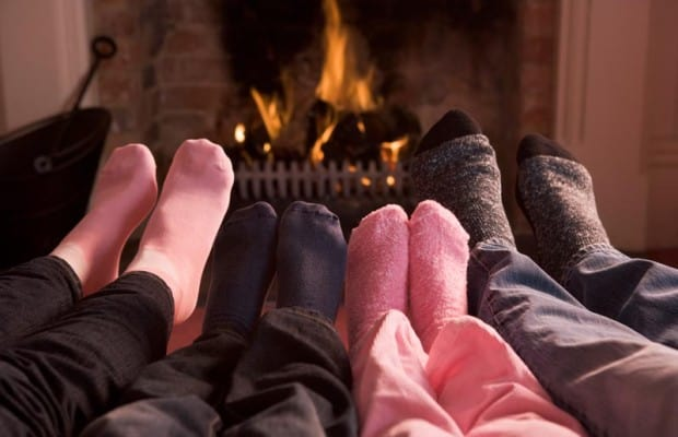 sock covered feet in front of fireplace